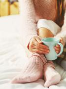 Woman relaxing at cozy home atmosphere on the bed. Young woman with cup of mi - stock photo