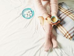 Woman relaxing at cozy home atmosphere on the bed. Young woman with cup of co Stock Photos