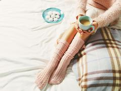 Woman relaxing at cozy home atmosphere on the bed. Young woman with cup of co - stock photo