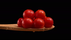 Wooden spoon spilling cherry tomatoes Stock Footage