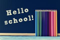 pencil crayons and text hello school written on a chalkboard - stock photo