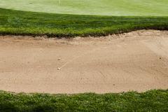 Golf ball on a bunker sand trap hazard in a golf course. Stock Photos