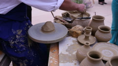 Pottery maker uses a kick wheel to hand mold a pot from clay Stock Footage