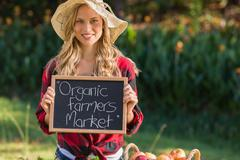 Pretty blonde selling organic vegetables at market Stock Photos