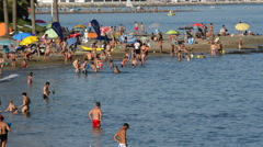 People bathing in a Benalmadena beach at sunset Stock Footage