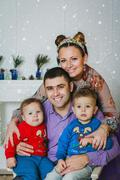 The happy family with two small boys smiling near the New Year tree together - stock photo