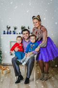 The happy family with two small boys smiling near the New Year tree together Stock Photos