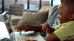 Father and son using laptop on the couch - stock footage