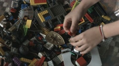 4 hands rummaging Lego pieces Stock Footage