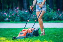 Woman mowing lawn in residential back garden on sunny day Stock Photos