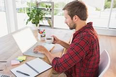 Creative businessman typing on laptop and holding hot beverage Stock Photos