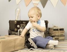 Old photo of sad baby looking at mail package indoors Stock Photos