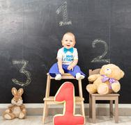 Happy one year old boy takes first place on the podium - stock photo