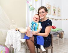 Happy young woman with little boy on her knees indoors Stock Photos