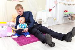 Father and little son read an old book sitting on the carpet Stock Photos