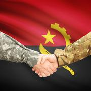 Men in uniform shaking hands with flag on background - Angola Stock Photos