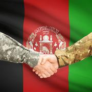 Men in uniform shaking hands with flag on background - Afghanistan - stock photo