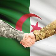 Men in uniform shaking hands with flag on background - Algeria - stock photo