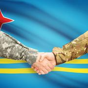 Men in uniform shaking hands with flag on background - Aruba - stock photo