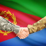 Men in uniform shaking hands with flag on background - Eritrea Stock Photos