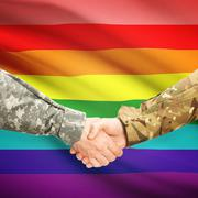 Men in uniform shaking hands with flag on background - LGBT people - stock photo