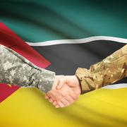Men in uniform shaking hands with flag on background - Mozambique - stock photo