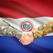 Stock Photo of Men in uniform shaking hands with flag on background - Paraguay
