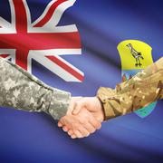 Men in uniform shaking hands with flag on background - Saint Helena Stock Photos