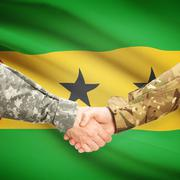 Stock Photo of Men in uniform shaking hands with flag on background - Sao Tome and Principe
