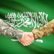 Men in uniform shaking hands with flag on background - Saudi Arabia - stock photo
