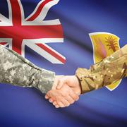 Men in uniform shaking hands with flag on background - Turks and Caicos Islan - stock photo