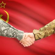 Stock Photo of Men in uniform shaking hands with flag on background - USSR