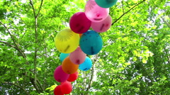 Balloons flutter  in the wind on the green foliage background Stock Footage