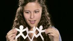 Beautiful young woman goes from frowning to delight after opening paper cutout Stock Footage