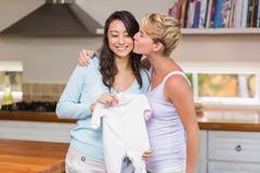 Pregnant woman receiving a baby clothe - stock photo