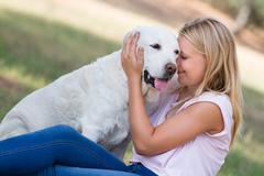 Blond teenager with old senior labrador dog in the park, selective focus Stock Photos