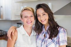 Smiling lesbian couple with arms around Stock Photos