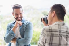 Homosexual couple men taking photo a digital camera Stock Photos
