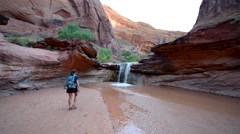 Girl Hiker walking towards the waterfall Coyote Gulch Escalante Stock Footage