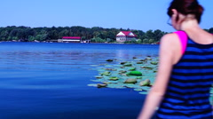 Holiday, lacustrine landscape.Woman looking out to the lake, relaxing and yawing Stock Footage