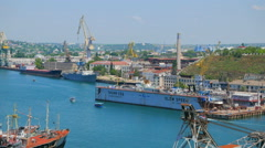 Harbor cranes, ships at anchor, and a floating dock. Sea Port of of Sevastopol. - stock footage