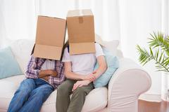 Homosexual couple wearing boxes over head Stock Photos