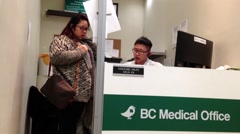 Young worker at work as receptionist inside BC medicial office - stock footage