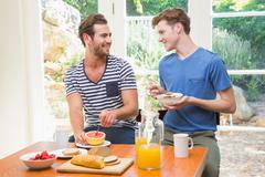 Happy homosexual couple having breakfast and looking at each other Stock Photos