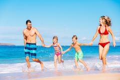 Happy Family Having Fun on the Beach Stock Photos