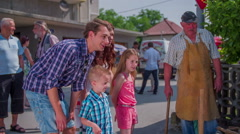Family is looking careful on blacksmith working on fair Stock Footage