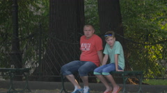 Father and son sitting on a bench in Krakow Stock Footage