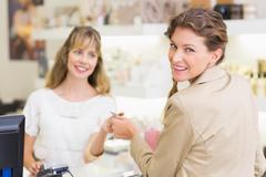 Beautiful customer at cash register giving credit card - stock photo