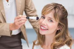 Stock Photo of Beautiful woman getting makeup applied