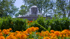 The fountain surrounded by flowers. Filmed with shallow depth of field. Stock Footage